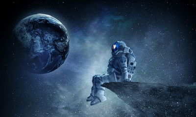 Fototapete - Spaceman on rock edge. Mixed media