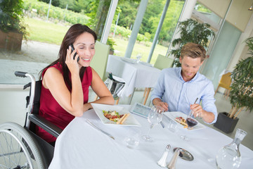 couple sitting at the restaurant the woman is disabled