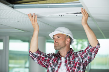 man installing suspended ceiling in house