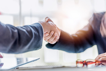 businessman and businesswoman shaking hands during a meeting in the office