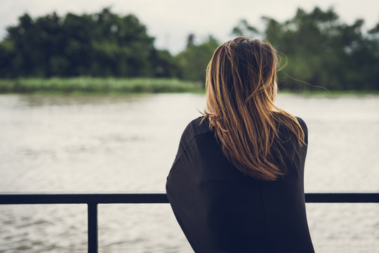 Lonely woman sitting and looking at the river