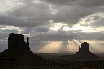 Monument Valley Right Mitten silhouetted in the first light flare on the morning sun light