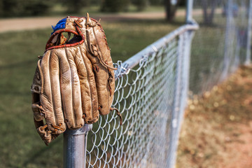An old scuffed leather baseball glove hanging on the post of a chain link fence