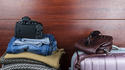Women's things lie at the closet with things with suitcase and women's bag and camera the concept of preparing for a trip
