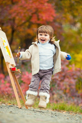 Cheerful little girl in a jump with a brush and paint, draws in the park of autumn leaves, painting of the Little Child