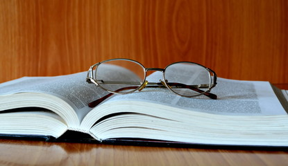 open thick vintage book with glasses on wooden table