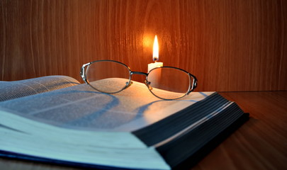 luminous in the dark burning candle over old thick open book on which glasses