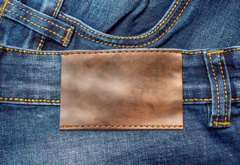 Brown leather label on a blue jeans. Close up.