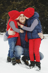 Father and his two sons having fun in winter in snow forest