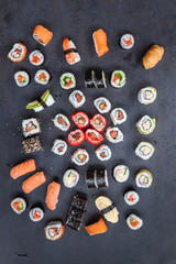 A variety of sushi with wooden desk on black slate background. Asian food frame. Dinner party.Top view. Copy space, overhead, flat lay