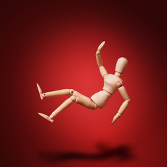 Wooden Mannequin on red background fall down. Safety first concept