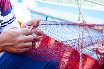 Fisherman is fixing the fish net