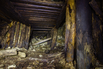 Abandoned old chromite mine shaft tunnel with wooden timbering