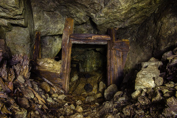 Underground abandoned old mine shaft iron copper gold ore tunnel gallery with wooden stands timbering