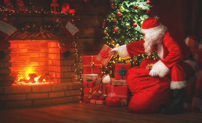 Merry Christmas! santa claus near the fireplace and tree with gifts