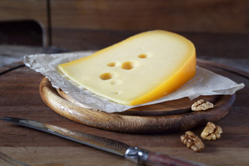 Cheese and walnuts on a wooden cutting board