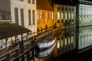 Boat at night on a quiet river in Bruges (Belgium)
