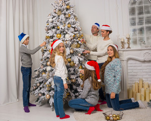 Children and adults are decorate a Christmas tree