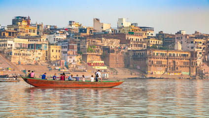 Varanasi city with old architectural buildings and ancient temples with tourists boat along the Ganges river ghat.