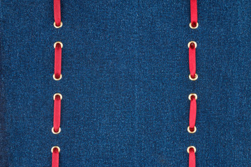 Two red ribbons are inserted into the denim fabric.
