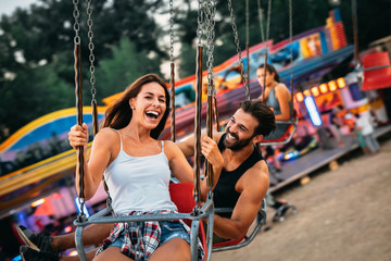 Young couple enjoying on the swings Wall mural
