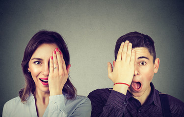Young surprised couple man and woman looking at camera