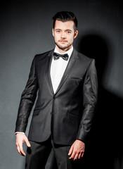 portrait of confident handsome man in black suit with bowtie