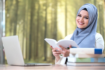 Pretty woman wearing hijab in front of laptop