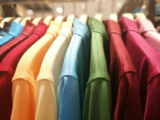 Mens shirts in different colors on hangers in a retail clothes store