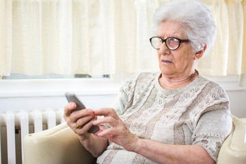 Confused senior woman using mobile phone.