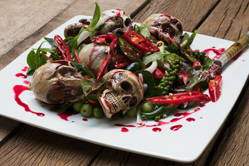 Spicy skulls on white dish on wooden table.Food for halloween and selective focus.
