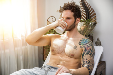 Shirtless sexy male model lying alone on couch in his living-room, drinking from a cup, looking away with a seductive attitude