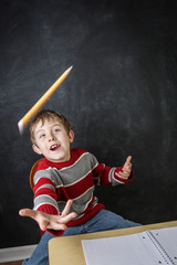 Young bored boy throwing his pencil in the air