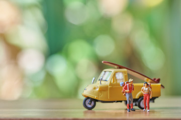Miniature 2 people standing travel planner with yellow toy car model as background travel concept with copy space.
