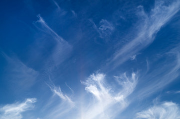 White striped curled clouds on the blue sky