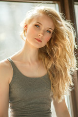 Romantic blonde. Young beautiful cute woman. Beauty girl with long shiny hair, glowing skin and voluminous haircut