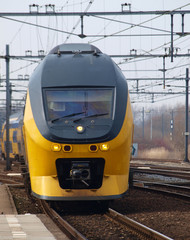 Double decker intercity arriving along platform om station of Gouda