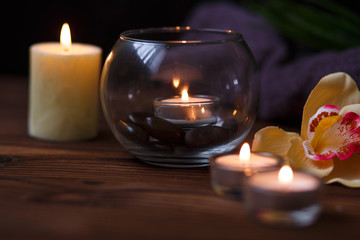 A candle in a glass vase, decoration and various interesting elements on a dark wooden background. Candles burning. Set for spa and massage. stones for massage