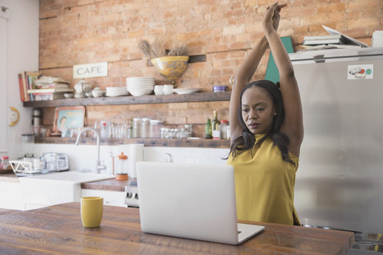 Businesswoman stretching her hands while working on laptop at home