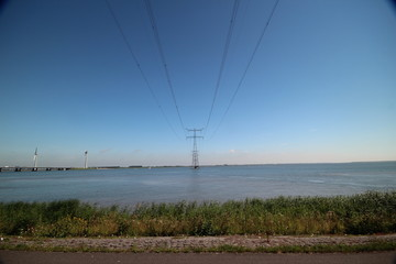 High voltage power line high above a lake in Netherlands with blue sky