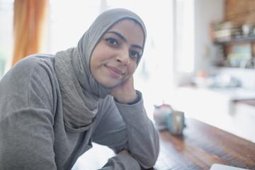 Muslim businesswoman wearing a hijab in her kitchen