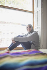 Muslim woman wearing a hijab sitting in a window sill