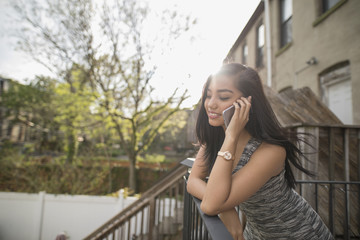 Young woman using her smart phone on her balcony