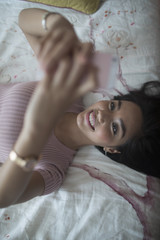Young woman using her Smartphone on her bed