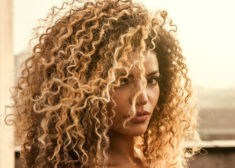 Beautiful woman with gorgeous curly hair in the sunlight