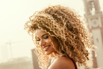 Gorgeous and happy woman portrait with beautiful curly hair smiling