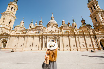 Young woman tourist in sunhat standing back in front of the famous cathedral on the central square during the sunny weather in Zaragoza city, Spain