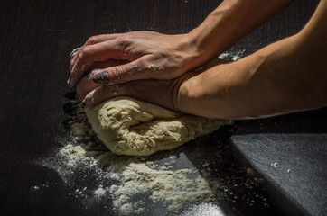 Female hands knead dough from flour for baking in the kitchen, handmade
