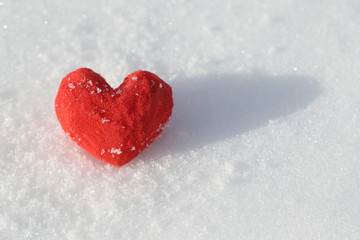 On the snow lies a red heart made of foam rubber. Template for a holiday card with a white texture and free space for text.