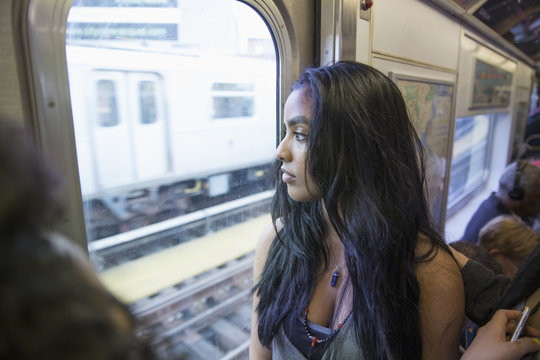 Young woman looking out the window of a train in Queens, New York